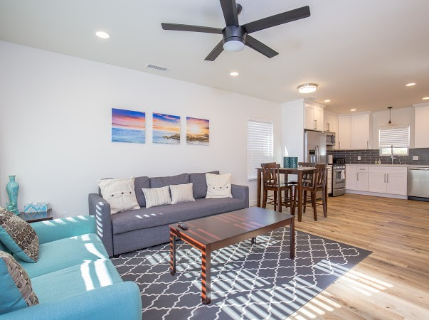 Open concept Kitchen, Dining and Living room has a sofa sleeper, Large Wall Mounted TV, lots of light from the glass door and large window!